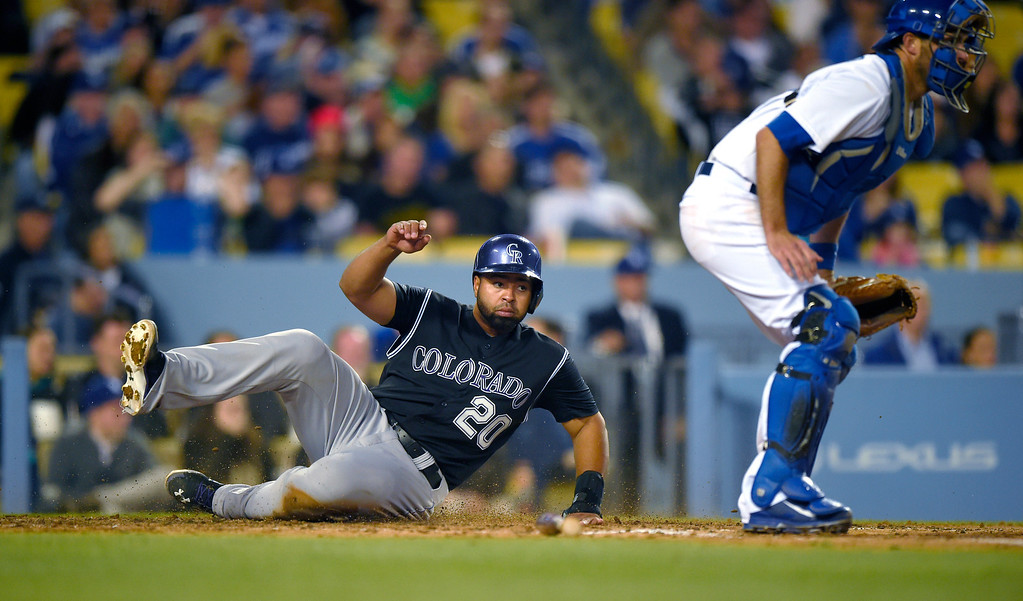 . Colorado Rockies\' Wilin Rosario, left, scores on a single by Justin Morneau as Los Angeles Dodgers catcher Drew Butera stands near the plaet during the fifth inning of a baseball game, Saturday, April 26, 2014, in Los Angeles. (AP Photo/Mark J. Terrill)