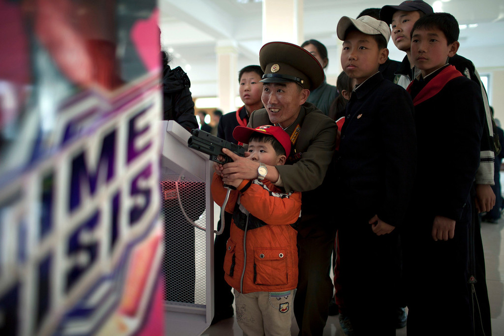 """. A North Korean military officer plays a game called \""""Time Crisis\"""" with his son at an amusement park in Pyongyang, North Korea, Tuesday, April 16, 2013. (AP Photo/Alexander F. Yuan)"""