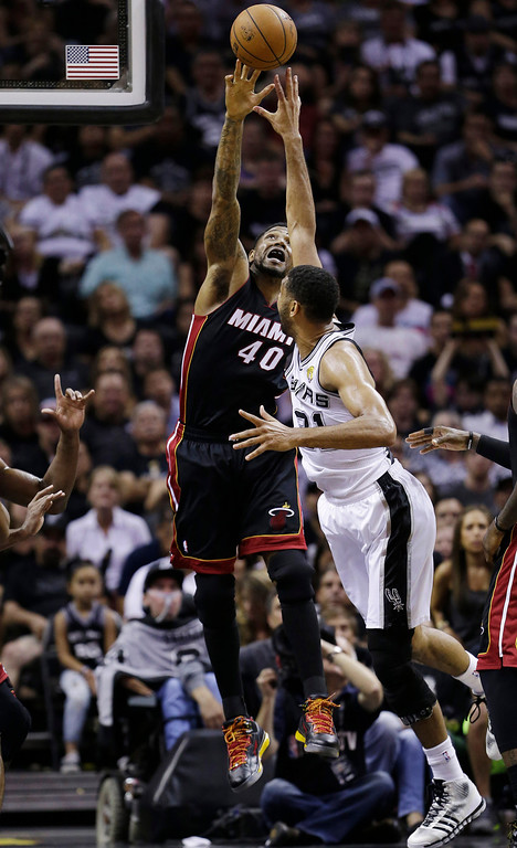 . Miami Heat forward Udonis Haslem (40) blocks a shot by San Antonio Spurs forward Tim Duncan (21) during the first half in Game 5 of the NBA basketball finals on Sunday, June 15, 2014, in San Antonio. (AP Photo/David J. Phillip)
