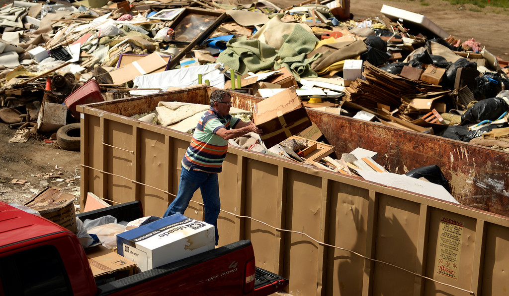 . BOULDER, CO - SEPTEMBER 18: Boulder resident, Robert Croft, helps neighbors unload belongings that were destroyed in the flood at a dump in Boulder, September 18, 2013. Residents start to clean up after a massive flood hit the area. (Photo By RJ Sangosti/The Denver Post)