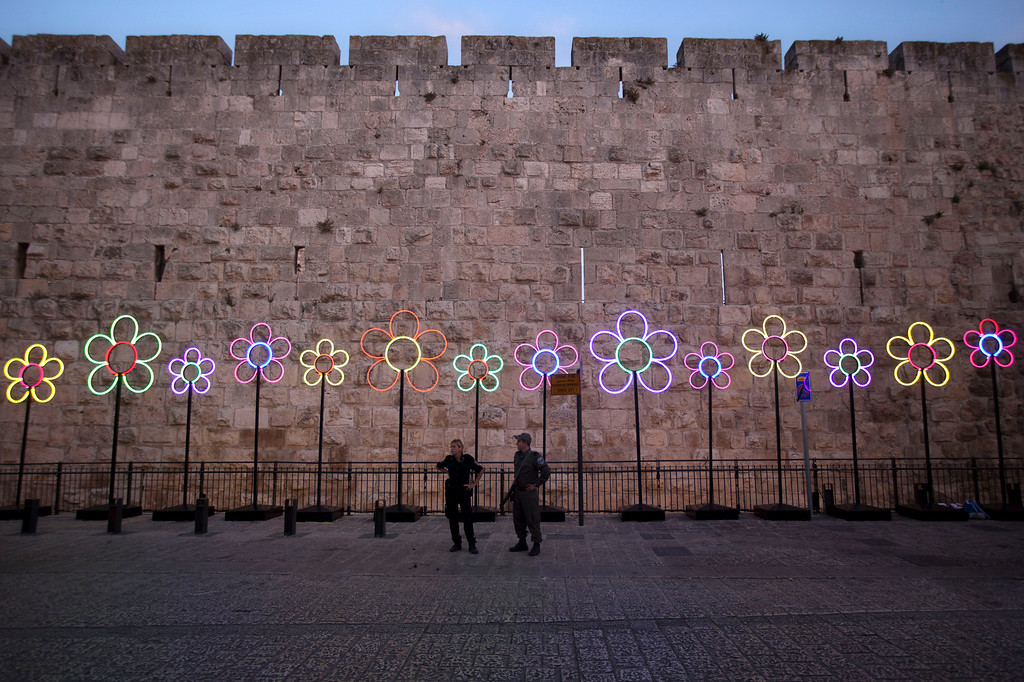 . Israeli police officers stand guard near a light installation inside the Jaffa gate during the fifth annual Festival of Light in Jerusalem\'s Old City,  Wednesday, June 5, 2013. (AP Photo/Sebastian Scheiner)