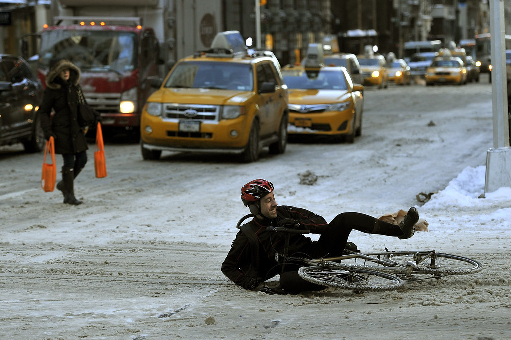 . A man falls on the ice and snow along  5th Avenue January 22, 2014 in New York. The northeastern US shivered amid heavy snowfall and far below average temperatures in a storm that grounded thousands of flights and triggered traffic chaos.   AFP PHOTO / TIMOTHY CLARY/AFP/Getty Images