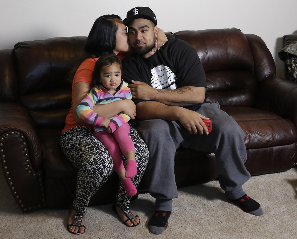 . Star Lotulelei receives a kiss from his wife Fuiva, who holds their daughter Pesatina, 1, after being selected 14th overall by the Carolina Panthers during an NFL football draft party at their home, Thursday, April 25, 2013, in South Jordan, Utah.  (AP Photo/Rick Bowmer)