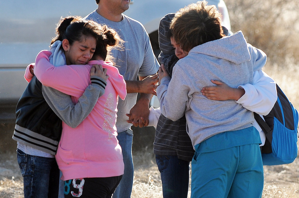 . Students are reunited with family following a shooting at Berrendo Middle School, Tuesday, Jan. 14, 2014, in Roswell, N.M. Roswell police said the suspected shooter was arrested at the school, but authorities have not said if there were any injuries. The school has been placed on lockdown. No other details are yet available. (AP Photo/Roswell Daily Record, Mark Wilson)