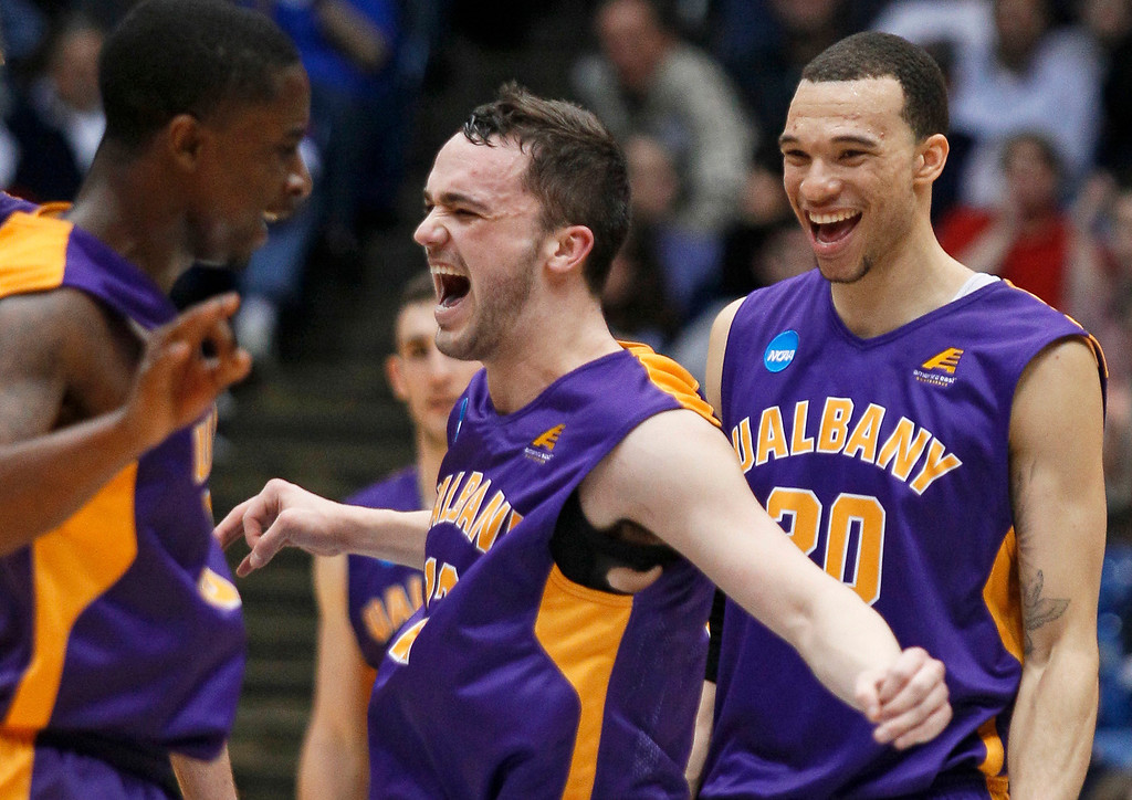 . Albany guard Peter Hooley, center, celebrates with guard D.J. Evans, left, and forward Gary Johnson after Albany defeated Mount St. Mary\'s 71-64 in a first-round game of the NCAA college basketball tournament, Tuesday, March 18, 2014, in Dayton, Ohio. (AP Photo/Skip Peterson)