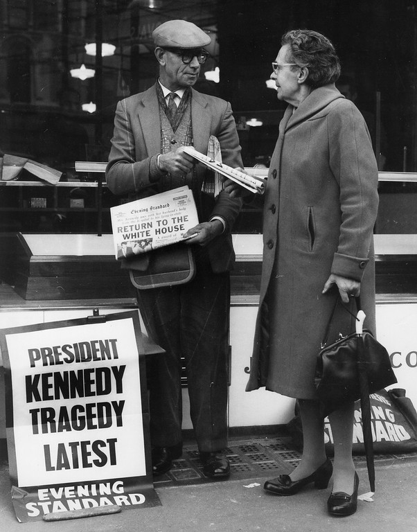 . A woman buys a copy of the Evening Standard from a street vendor on Nov. 23, 1963. Trevor Humphries, Central Press/Getty Images)