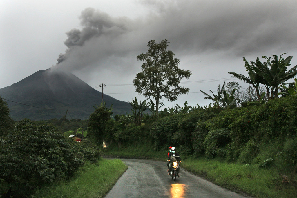 . Motorists ride pass by as Mount Sinabung spews volcanic ash into the air in Tiga Pancur, North Sumatra, Indonesia, Tuesday, Nov. 26, 2013.  (AP Photo/Binsar Bakkara)