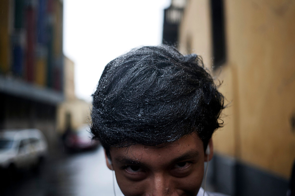 . In this June 28, 2013 photo, a man leans forward to show the drops of water in his hair during an intense drizzle in downtown Lima, Peru. For roughly four months a year, the sun abandons Peru\'s seaside desert capital, suffocating it under a ponderous gray cloudbank and fog that coats the city with nighttime drizzles. Barometers often read 100 percent humidity, and rheumatoid and bronchial ailments soar in the city of 9 million. (AP Photo/Rodrigo Abd)