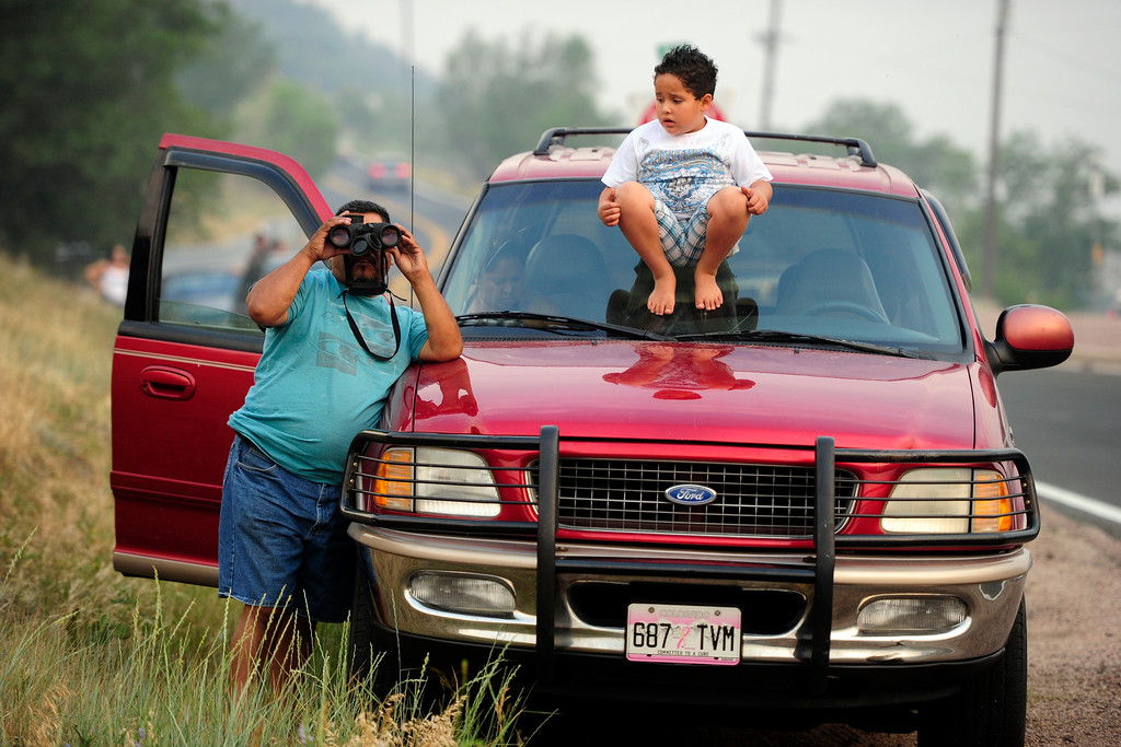 . Salvador Perez and his nephew Diego Ortiz, 6, watch as the Waldo Canyon Fire burns outside of Colorado Springs on Sunday, June 24, 2012. AAron Ontiveroz, The Denver Post