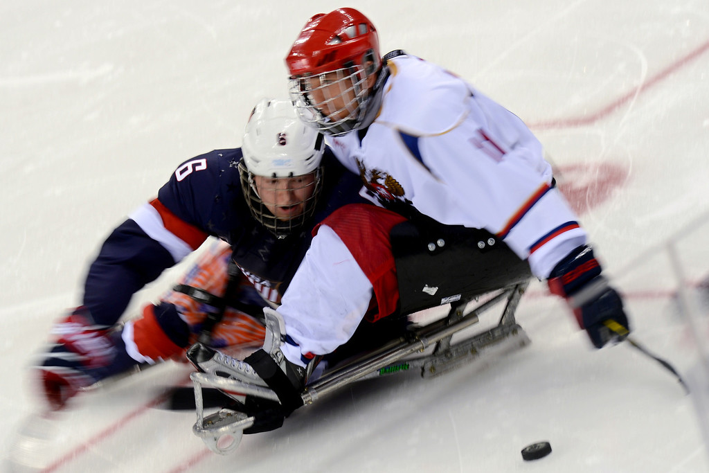 . US Declan Farmer (L) vies with Russia\'s Alexey Amosov during the ice sledge hockey match Russia vs USA during the XI Paralympic Olympic games at the Shayba stadium, near Sochi on March 11, 2014. AFP PHOTO / KIRILL KUDRYAVTSEV
