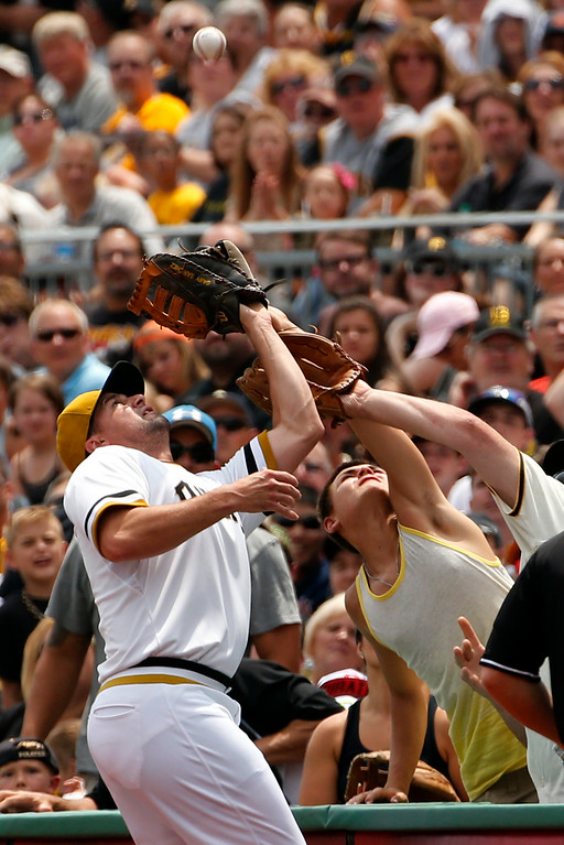 . Pittsburgh Pirates first baseman Gaby Sanchez, left, makes a foul ball catch hit by Colorado Rockies\' Drew Stubbs to end the first inning of a baseball game in Pittsburgh, Sunday, July 20, 2014. (AP Photo/Gene J. Puskar)