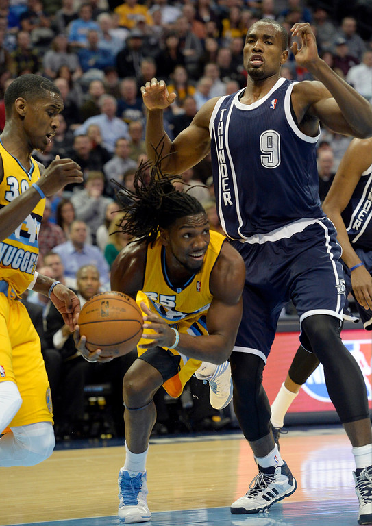 . Denver Nuggets power forward Kenneth Faried (35) looks to pass the ball with Oklahoma City Thunder power forward Serge Ibaka (9) defending as he falls during the first quarter January 9, 2014 at Pepsi Center. (Photo by John Leyba/The Denver Post)