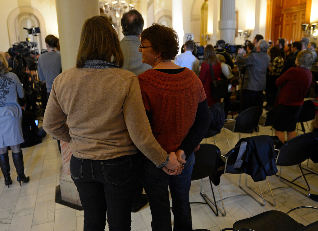 . DENVER, CO. - MARCH 20: Megan Sullivan, left, hold hands with her mother Terry, who\'s son was killed in the Aurora theater shooting, during a press conference at the Colorado State Capitol, March, 20, 2013. Colorado Governor John Hickenlooper earlier signing three gun control measures making stricter gun laws in Colorado. (Photo By RJ Sangosti/The Denver Post)