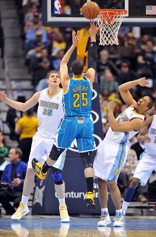 . DENVER, CO. - FEBRUARY 01: Austin Rivers of New Orleans Hornets #25 jumps for the basket over Timofey Mozgov #25 and Andre Miller #24 of Denver Nuggets in the 1st half of the game on February 1, 2013 at the Pepsi Center in Denver, Colorado. (Photo By Hyoung Chang/The Denver Post)