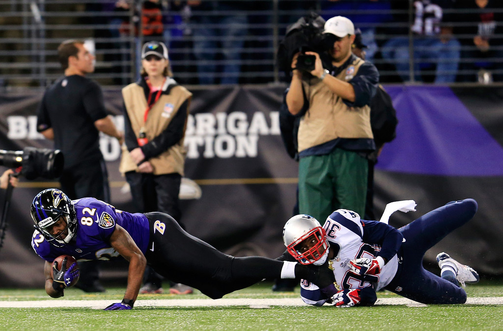 . Wide receiver Torrey Smith #82 of the Baltimore Ravens is tackled by strong safety Duron Harmon #30 of the New England Patriots after catching a second half pass at M&T Bank Stadium on December 22, 2013 in Baltimore, Maryland.  (Photo by Rob Carr/Getty Images)