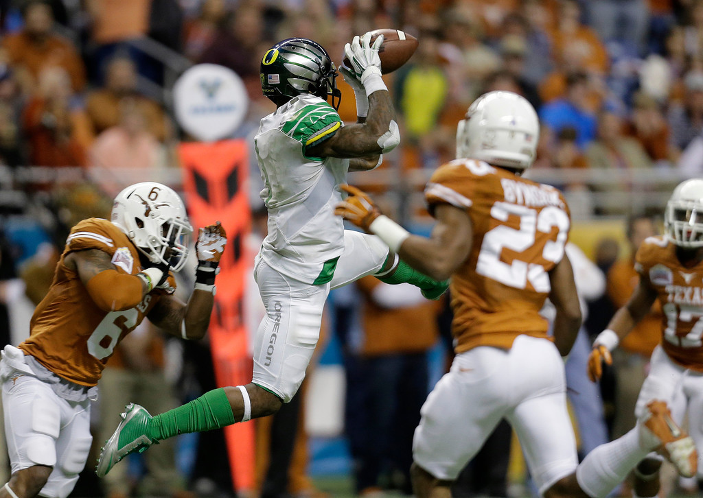 . Oregon\'s Josh Huff, center, pulls in a pass as Texas\' Quandre Diggs (6) defends during the second half of the Valero Alamo Bowl NCAA college football game, Monday,  Dec. 30, 2013, in San Antonio. Oregon won 30-7. (AP Photo/Eric Gay)