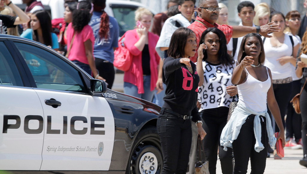 . Students point to their waiting parents outside Spring High School Wednesday, Sept. 4, 2013, in Spring, Texas.  (AP Photo/David J. Phillip)