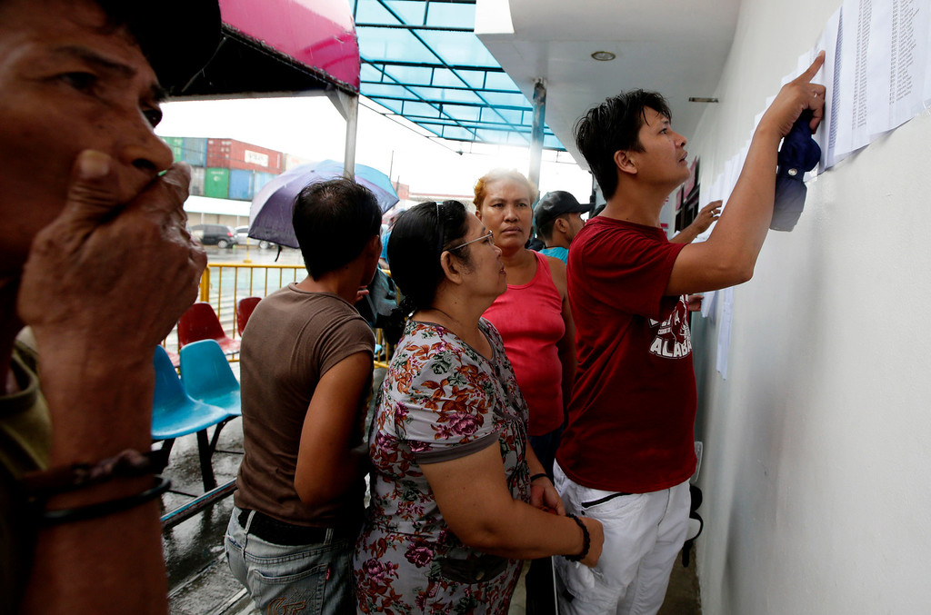 . Relatives check the lists of survivors and the still-missing passengers and crew of the ill-fated passenger ferry MV Thomas Aquinas, outside the ticketing office of a shipping company, Saturday Aug. 17, 2013, a day after the ferry collided with a cargo ship, the MV Sulpicio Express Siete, off the waters of Talisay city, Cebu province in central Philippines. Divers combed through the sunken ferry Saturday in search of dozens of people missing after the collision that sent passengers jumping into the ocean and leaving many others trapped. At least 31 were confirmed dead and hundreds rescued. (AP Photo/Bullit Marquez)