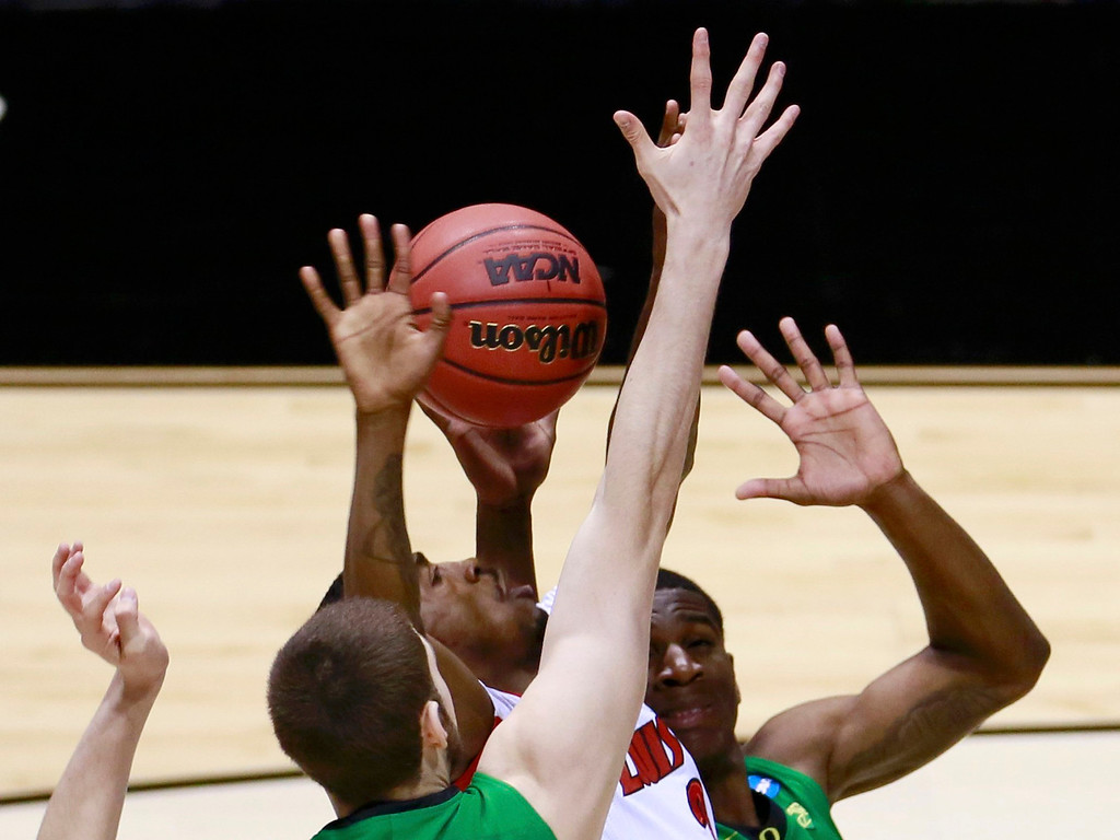 . Louisville Cardinals guard Russ Smith (2) tries to go to the basket between Oregon Ducks forward Ben Carter (L) and Damyean Dotson (R) during their Midwest Regional NCAA men\'s basketball game in Indianapolis, Indiana, March 29, 2013. REUTERS/Brent Smith
