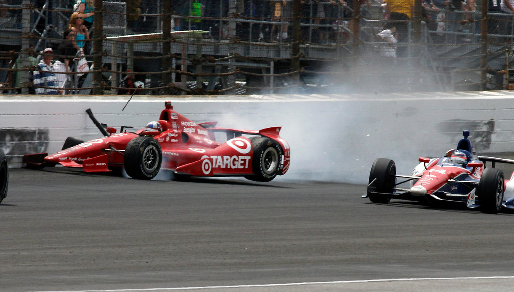 . Dario Franchitti, left, of Scotland, hits the wall on the first turn in front of Takuma Sato, of Japan, to bring out the final caution during Indianapolis 500 auto race at Indianapolis Motor Speedway in Indianapolis, Sunday, May 26, 2013. (AP Photo/Tom Hemmer)