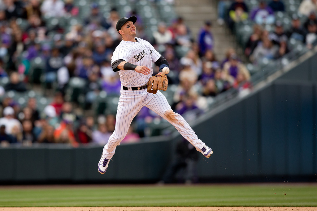 . Shortstop Troy Tulowitzki #2 of the Colorado Rockies makes a leaping throw to second base for an out during the eighth inning against the Arizona Diamondbacks at Coors Field on April 6, 2014 in Denver, Colorado. The Diamondbacks defeated the Rockies 5-3. (Photo by Justin Edmonds/Getty Images)