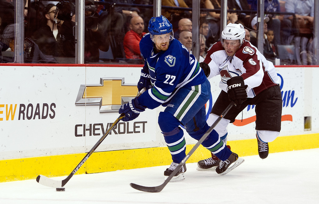 . Daniel Sedin #22 of the Vancouver Canucks looks to make a pass while being checked by Erik Johnson #6 of the Colorado Avalanche during the second period in NHL action on April 10, 2014 at Rogers Arena in Vancouver, British Columbia, Canada.  (Photo by Rich Lam/Getty Images)