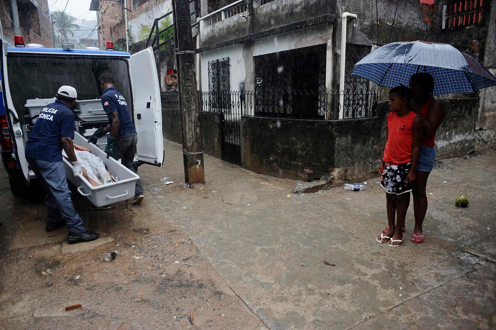 . The body of a person identified by the police as a transvestite named Rodrigo, is removed by police forensic workers from the street where he was shot in the Alto do Cabrito slum of Salvador, Bahia State, March 30, 2013. One of Brazil\'s main tourist destinations and a 2014 World Cup host city, Salvador suffers from an unprecedented wave of violence with an increase of over 250% in the murder rate, according to the Brazilian Center for Latin American Studies (CEBELA). Picture taken March 30, 2013.  REUTERS/Lunae Parracho