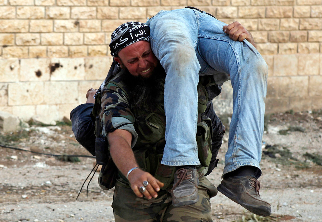 ". A Free Syrian Army fighter reacts as he carries the body of a fellow fighter after he was killed by a sniper loyal to Syria\'s President Bashar al-Assad in Khan al-Assal area November 10, 2012. Picture taken November 10, 2012. The headband on the fighter reads, ""God is great\"". REUTERS/Zain Karam"