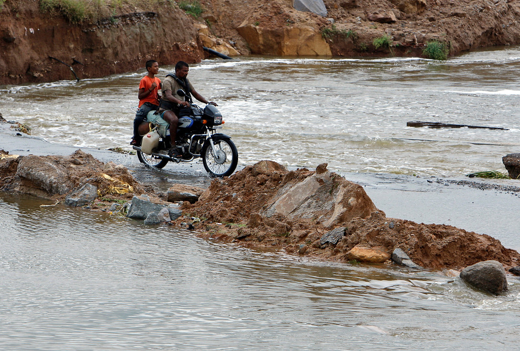 . Indians ride a motorbike through a flood-damaged road on the outskirts of Hyderabad, in the southern Indian state of Andhra Pradesh, Saturday, Oct. 26, 2013. Days of torrential rains have unleashed floods in the states of Andhra Pradesh and Orissa, killing dozens of people and forced the evacuation of more than 70,000 others from hundreds of low-lying villages. (AP Photo/Mahesh Kumar A.)