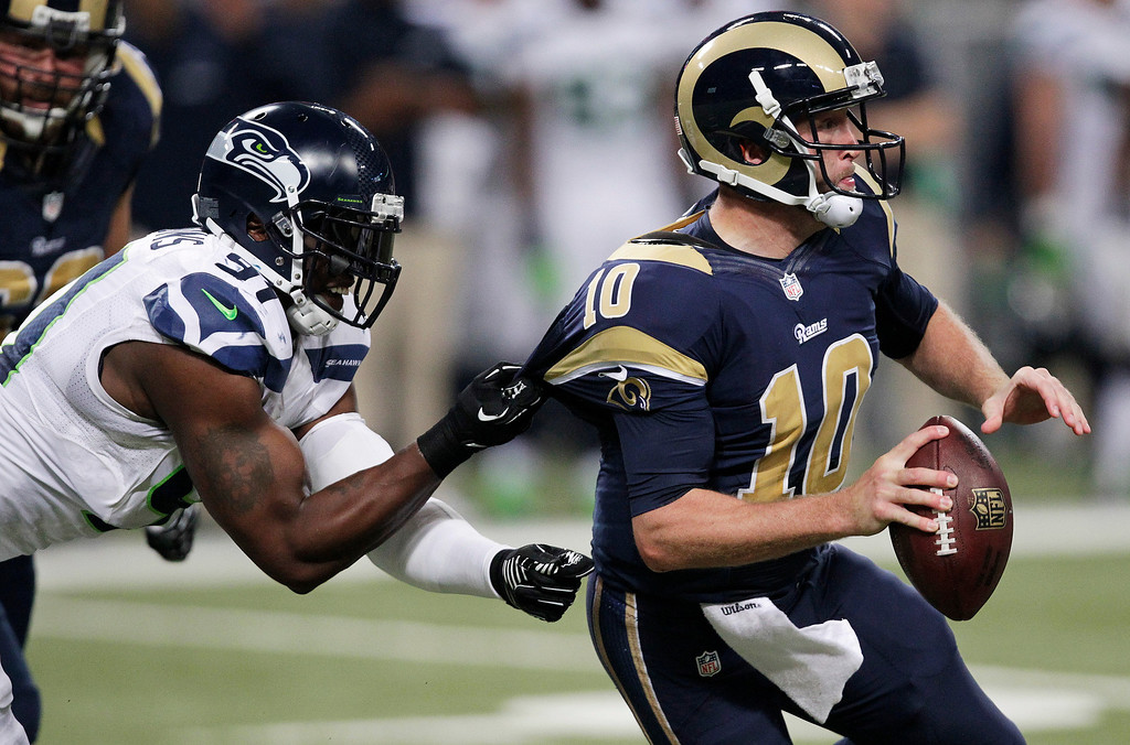 . Seattle Seahawks defensive end Chris Clemons (91) grabs on to St. Louis Rams quarterback Kellen Clemens\' jersey during the second half of an NFL football game, Monday, Oct. 28, 2013, in St. Louis. (AP Photo/Tom Gannam)