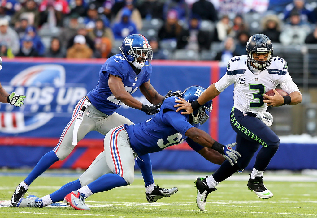 . Russell Wilson #3 of the Seattle Seahawks scrambles with the ball as  Justin Tuck #91 of the New York Giants defends at MetLife Stadium on December 15, 2013 in East Rutherford, New Jersey.The Seattle Seahawks defeated the New York Giants 23-0.  (Photo by Elsa/Getty Images)