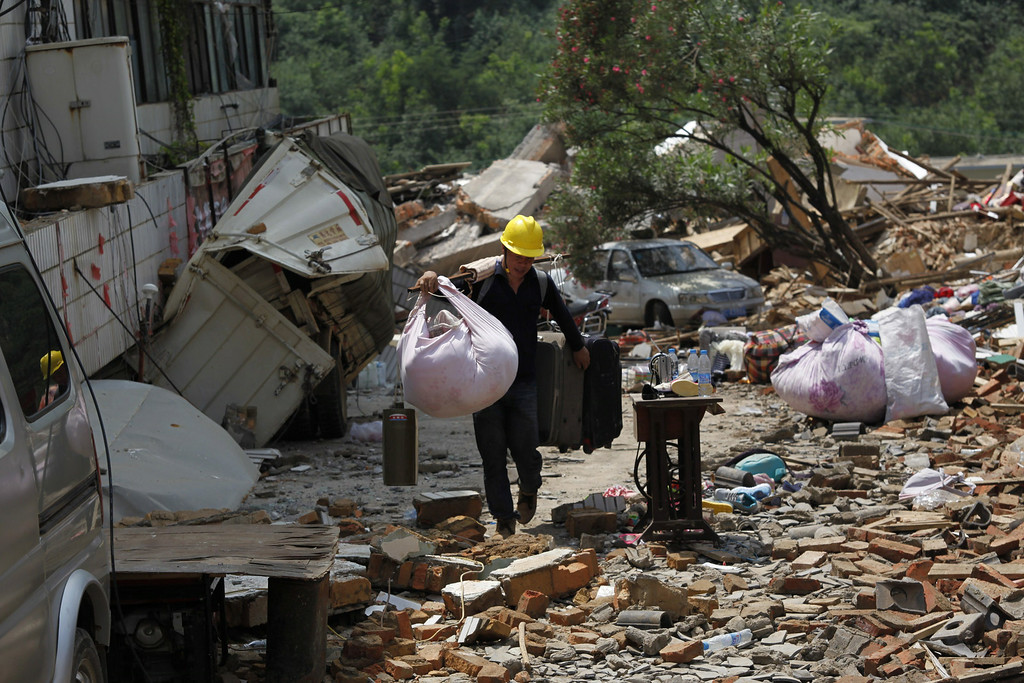 . A man carries his belongings following an earthquake at Longtoushan township of Ludian county in Zhaotong, southwest China\'s Yunnan province, on August 5, 2014. AFP PHOTOSTR/AFP/Getty Images