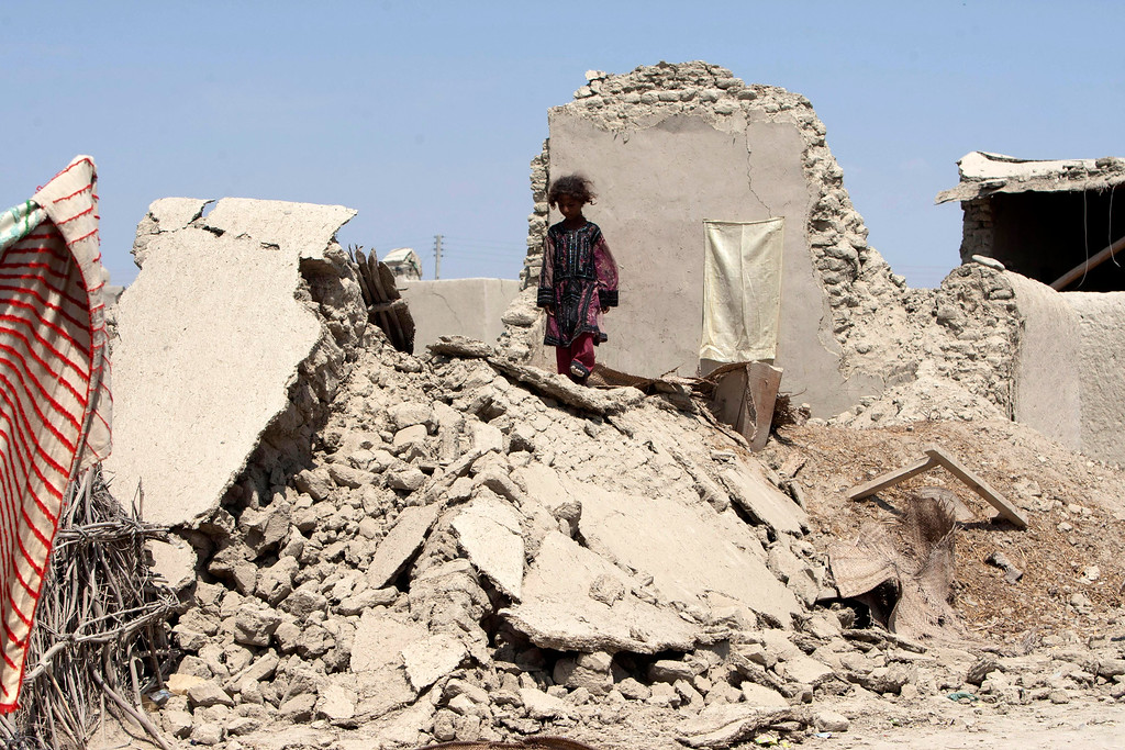 . A Pakistani girl walks on the rubble of a house destroyed following an earthquake in Labach, the remote district of Awaran in Baluchistan province, Pakistan, Thursday, Sept. 26, 2013. Two days after the tremor struck, rescuers were still struggling to help survivors. The death toll from the quake reached in hundreds on Thursday, with more than 500 people injured. (AP Photo/Shakil Adil)