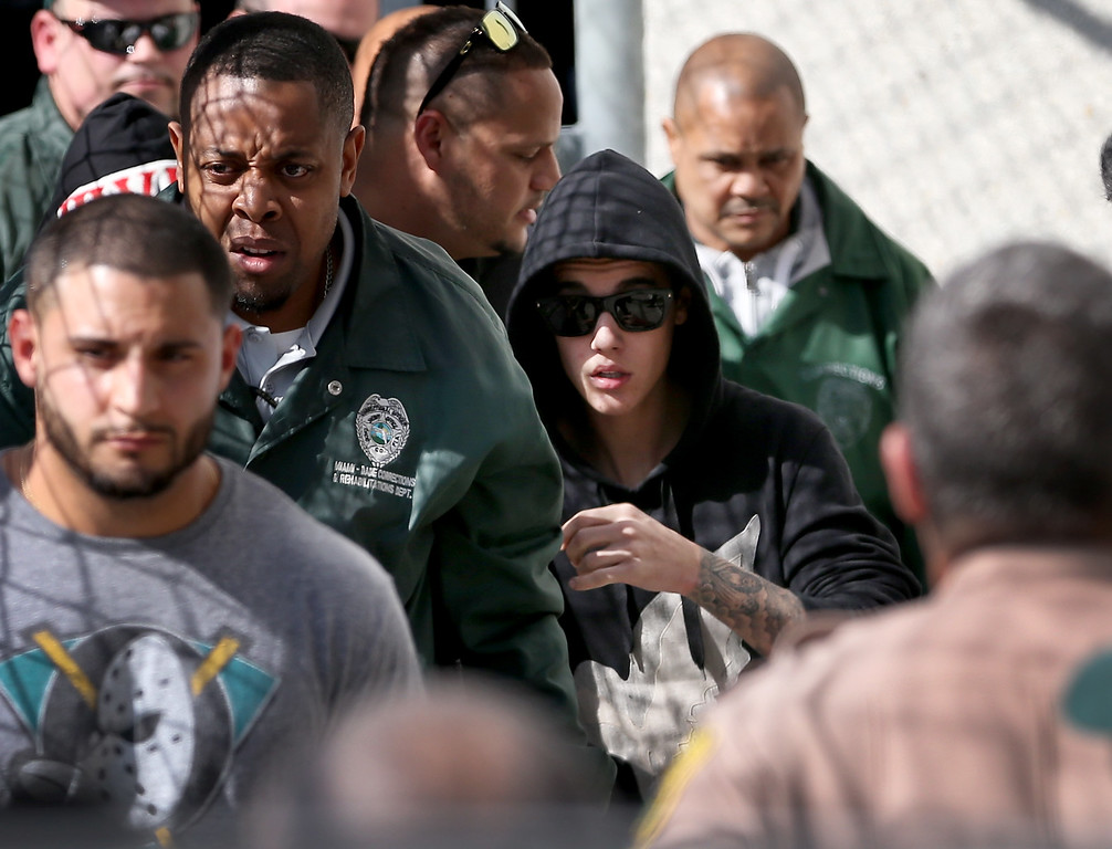 . Justin Bieber (R) exits from the Turner Guilford Knight Correctional Center on January 23, 2014 in Miami, Florida. Justin Bieber was charged with drunken driving, resisting arrest and driving without a valid license after Miami Beach police found the pop star street racing Thursday morning.  (Photo by Joe Raedle/Getty Images)