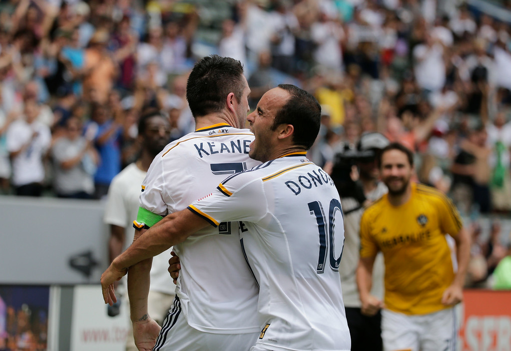 . Los Angeles Galaxy\'s Robbie Keane, left, of Ireland, and Landon Donovan celebrate a goal by Keane during the second half of an MLS soccer match against the Portland Timbers on Saturday, Aug. 2, 2014, in Carson, Calif. The Galaxy won 3-1. (AP Photo/Jae C. Hong)