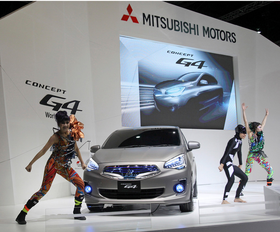 . Thai dancers perform around Mitsubishi Motors\' concept G4 subcompact on the press day of the Bangkok Motor Show in Bangkok, Thailand, Tuesday, March 26, 2013. The 34th running of the show is opened to the public from Wednesday. (AP Photo/Sakchai Lalit)