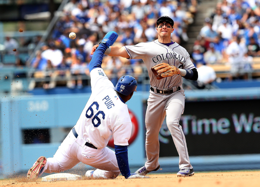 . Shortstop Troy Tulowitzki #2 of the Colorado Rockies throws to first to complete a double play after forcing out Yasiel Puig #66 of the Los Angeles Dodgers to end the third inning at Dodger Stadium on April 27, 2014 in Los Angeles, California.  (Photo by Stephen Dunn/Getty Images)