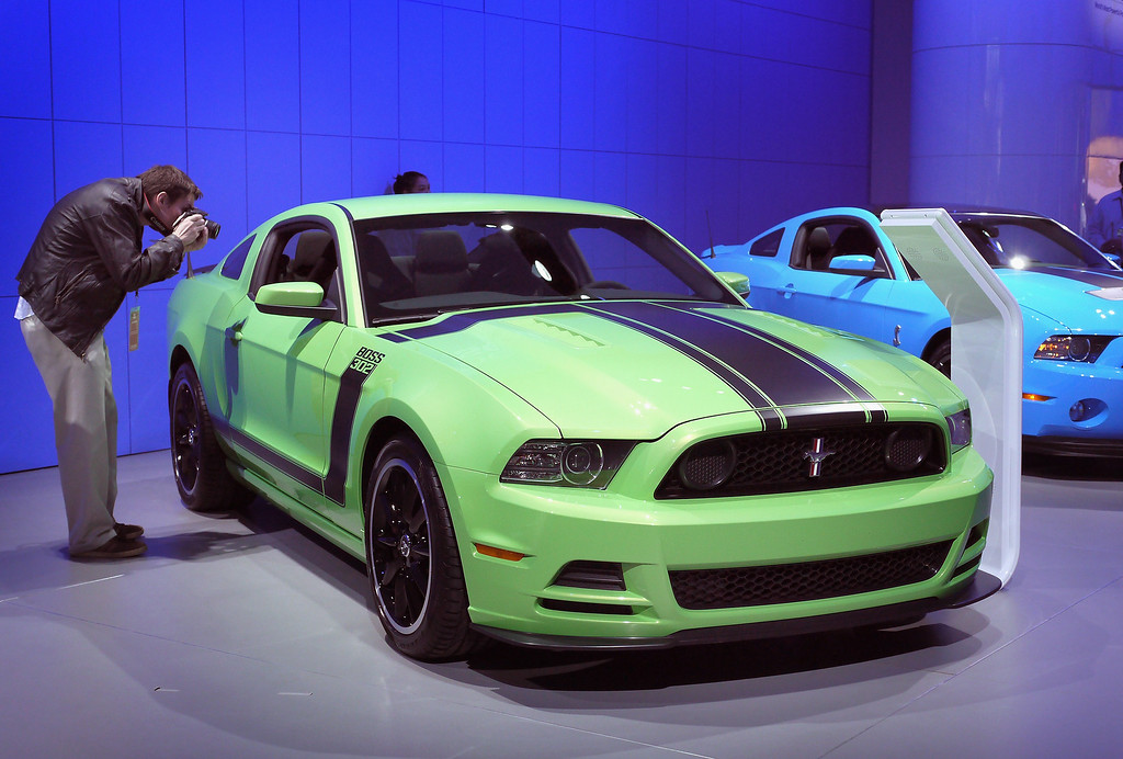 . A visitor photographs a Ford Mustang Boss 302 during the press preview at the North American International Auto Show at the COBO Center on January 10, 2012 in Detroit, Michigan.  (Photo by Scott Olson/Getty Images)