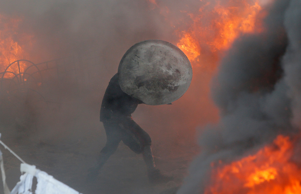 . A protester runs amidst fire during a clash with riot police in central Kiev, Ukraine, Saturday Jan. 25, 2014. Ukraine\'s Interior Ministry has accused protesters in Kiev of capturing two of its officers as violent clashes have resumed in the capital and anti-government riots spread across Ukraine. (AP Photo/Efrem Lukatsky)