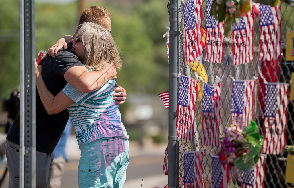 . Rhonda Tramel hugs an unidentified firefighter outside the Granite Mountain Interagency Hotshot Crew fire station Tuesday, July 2, 2013 in Prescott, Ariz. (AP Photo/Julie Jacobson)