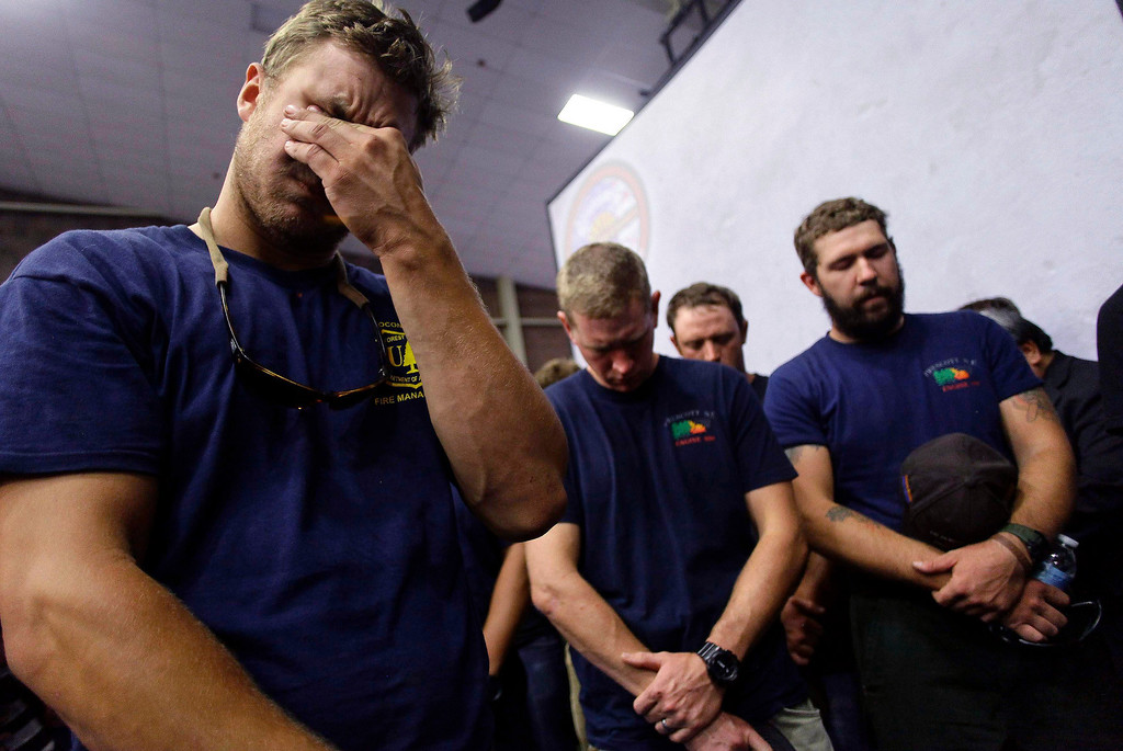 . Hotshot firefighters mourn during a moment of silence for the 19 firefighters who perished battling a fast-moving wildland fire at a memorial service, in Prescott, Arizona July 1, 2013.     REUTERS/Joshua Lott