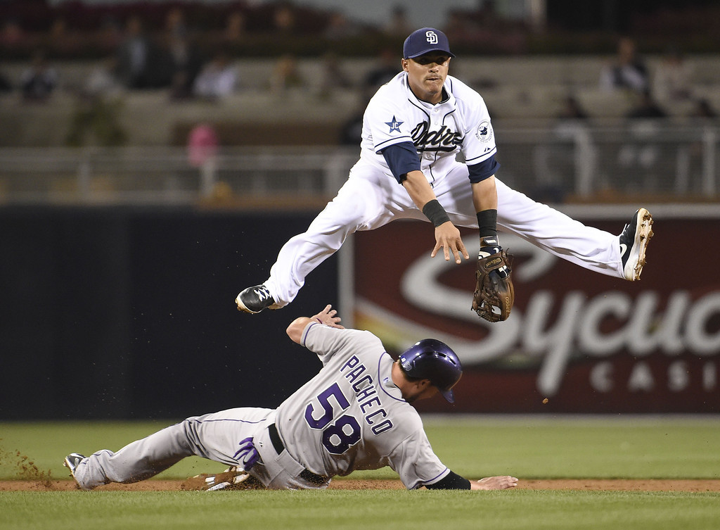 . SAN DIEGO, CA - APRIL 16:  Everth Cabrera #2 of the San Diego Padres jumps over Jordan Pacheco #58 of the Colorado Rockies as he tries to turn a double play during the third inning of a  baseball game at Petco Park April 16, 2014 in San Diego, California.  (Photo by Denis Poroy/Getty Images)