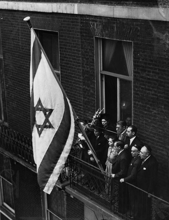 . 31st January 1949:  A Jewish flag is unfurled at the Israeli Embassy at Manchester Square, London, following Britain\'s recognition of the new state of Israel.  Embassy staff stand on the balcony.  (Photo by Fred Morley/Fox Photos/Getty Images)