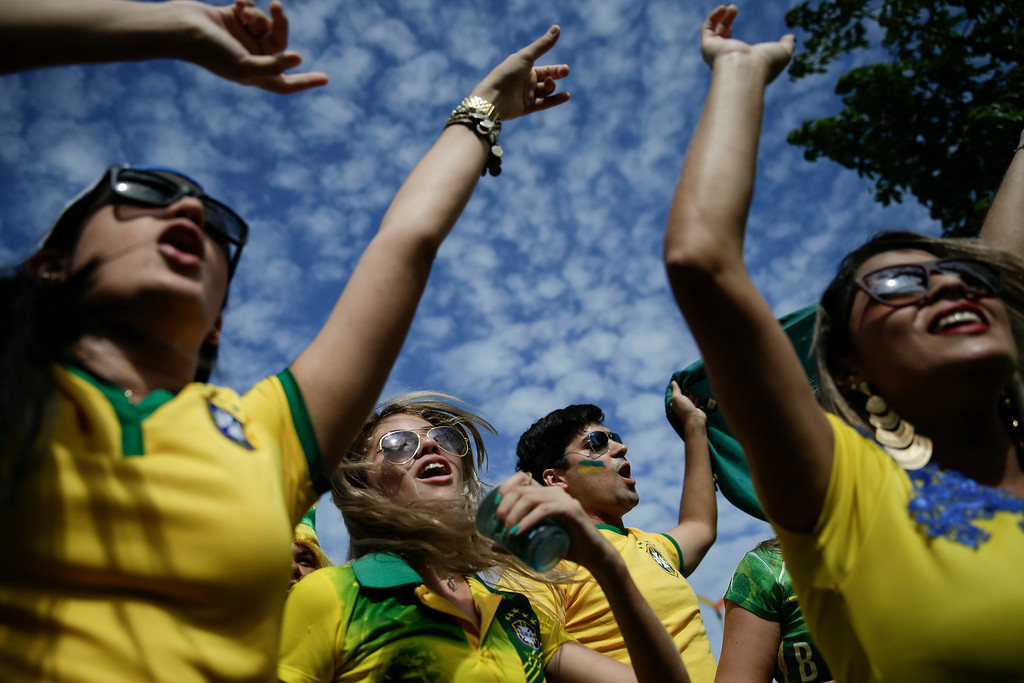 . Brazilian soccer fans rev themselves up as they wait to enter the Arena Castelao, for the World Cup quarterfinal match between Brazil and Colombia, in Fortaleza, Brazil, Friday, July 4, 2014. (AP Photo/Felipe Dana)