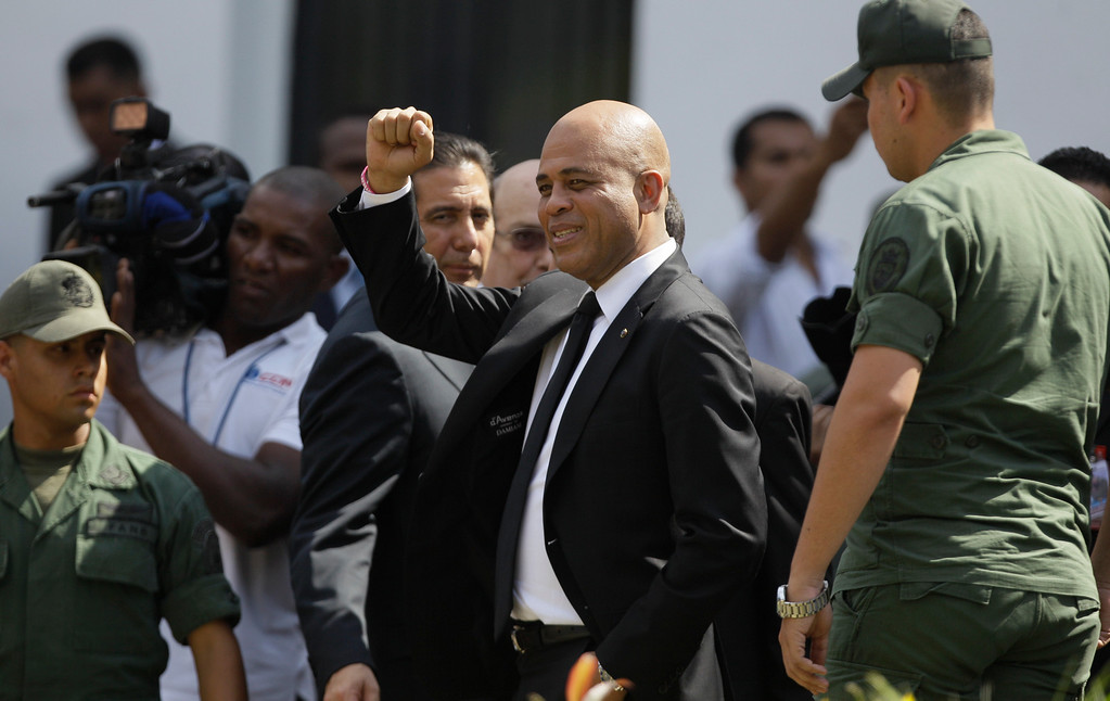 . Haiti\'s President Michel Martelly raises his fist after attending the funeral ceremony for Venezuela\'s late President Hugo Chavez at the military academy in Caracas, Venezuela, Friday, March 8, 2013.  (AP Photo/Fernando Llano)