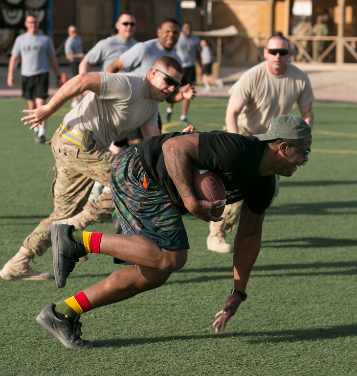. Denver Broncos linebacker Von Miller breaks away with the football during an impromptu touch football game with service members stationed in the Middle East during a stop on his week-long USO/NFL tour March 16, 2013.  USO Photo by Fred Greaves