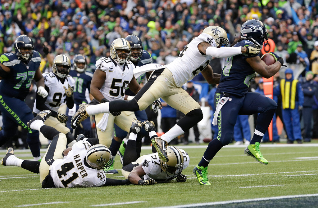 . Seattle Seahawks running back Marshawn Lynch, right, runs past New Orleans Saints cornerback Corey White (24) for a 15-yard touchdown during the second quarter of an NFC divisional playoff NFL football game in Seattle, Saturday, Jan. 11, 2014. (AP Photo/Elaine Thompson)