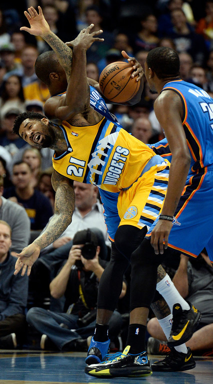 . Denver Nuggets small forward Wilson Chandler (21) gets tangled up with Oklahoma City Thunder power forward Serge Ibaka (9) as they battle for the ball during the first quarter December 17, 2013 at Pepsi Center. (Photo by John Leyba/The Denver Post)