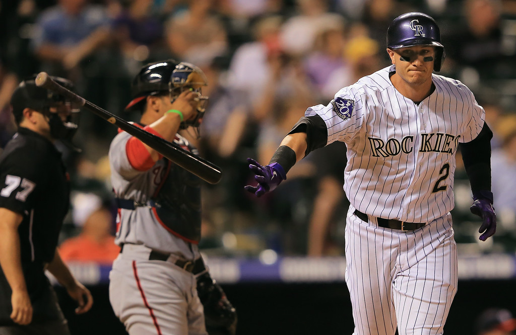 . Troy Tulowitzki #2 of the Colorado Rockies tosses his bat as he flies out against the Washington Nationals in the ninth inning at Coors Field on June 12, 2013 in Denver, Colorado. The Nationals defeated the Rockies 5-1.  (Photo by Doug Pensinger/Getty Images)
