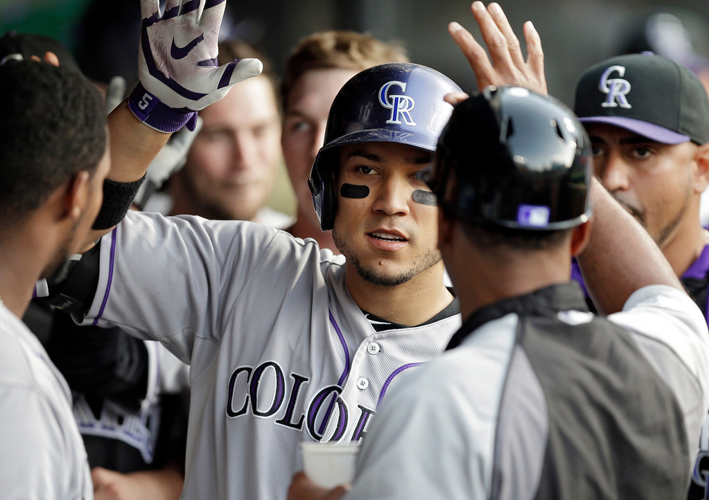 . Colorado Rockies\' Carlos Gonzalez is greeted in the dugout after a two-run home run against the Cleveland Indians in the fourth inning of a baseball game Friday, May 30, 2014, in Cleveland. (AP Photo/Mark Duncan)